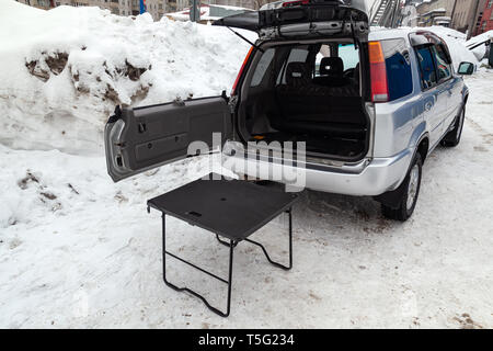 SUV car in silver color with opened trunk and table for picnic near it after cleaning before sale in a winter day and snow background - Stock Photo