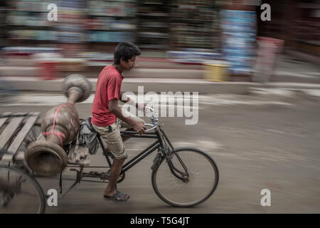 A boy on his rickshaw speeding through traffic in downtown Kathmandu - Stock Photo