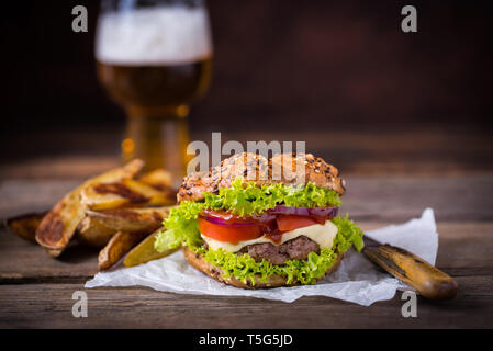 Home made hamburger with green salad on brown wooden background. - Stock Photo