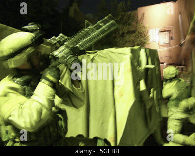 Baghdad, Baghdad, Iraq. 7th Nov, 2004. Soldiers from Charlie Troop, 1st Squadron, 7th Cavalry Regiment cover a house before a raid in Baghdad Nov. 7, 2004. The troop later detained two men who tested positive for recent exposure to explosive material. Credit: Bill Putnam/ZUMA Wire/Alamy Live News - Stock Photo