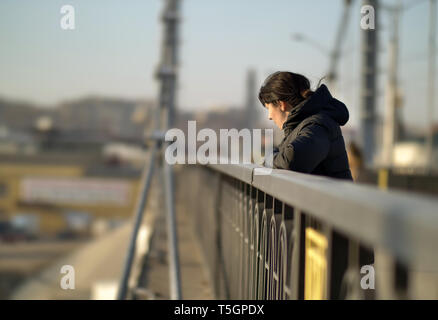 Lonely young girl stands on the bridge on a sunny day - Stock Photo