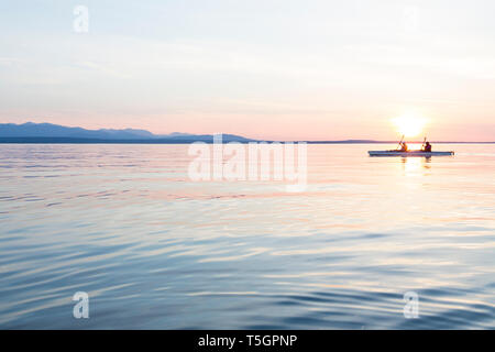 People women sea kayaking paddling boat in calm water at sunset. Active outdoor adventure water sports. Journey, destination, teamwork concepts. - Stock Photo