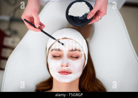 Hands of cosmetology specialist applying facial mask using brush, making skin hydrated and healthy. Attractive woman relaxing with closed eyes and - Stock Photo