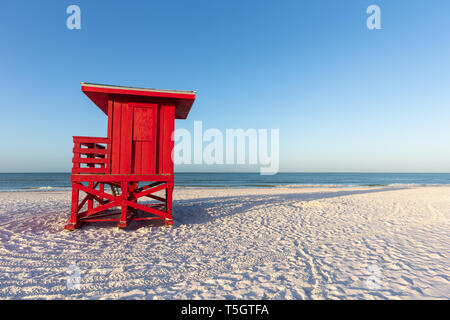 Red lifeguard tower on an early morning beach.  Copy space in the sky if needed. - Stock Photo