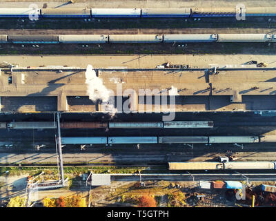 Aerial view of railroad yard with passenger and cargo trains on rail. - Stock Photo