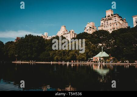 A reflecting lake in a park with tall buildings, trees and a beautiful sky - Stock Photo