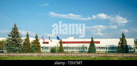 Friendship cooperation United States, French and European Union flags waving in front of Business factory industrial building in France - spring blue sky with scattered clouds