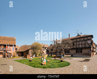 Bergheim, France - 19 Apr 2019: Kids playing near water fountain with multiple Easter decorations on the lawn - Stock Photo
