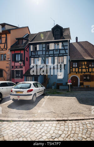 Bergheim, France - 19 Apr 2019: White Peugeot car parked in front of blue half timbered house of Bergheim village - Stock Photo