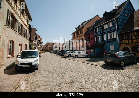 Bergheim, France - 19 Apr 2019: Beautiful Alsatian village of Bergehim with cars parked on central square and city-hall building in background  - Stock Photo