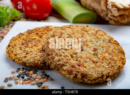 Tasty vegetarian food, raw burgers made from lentils legumes with vegetables ready for cooking, good for vegans - Stock Photo