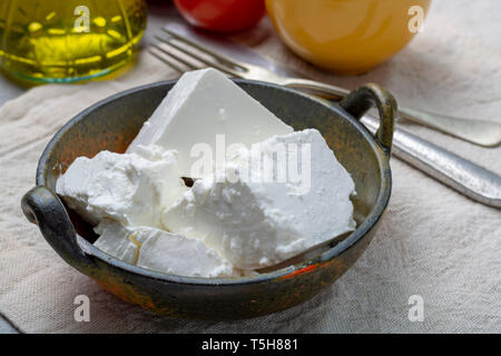 Fresh young soft white salted Feta cheese in bowl - Stock Photo