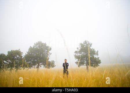 Man in Black Standing in Field