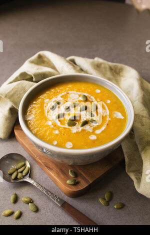 A bowl of pumpkin soup with a spoon and napkin and pumpkin seeds - Stock Photo