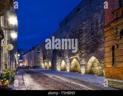 illuminated Tallinn old town buildings in the night. Medieval city wall and towers - Stock Photo