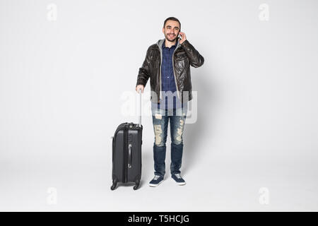 Young man with suitcase talking on the phone isolated over white background. Young traveler rolls the suitcase and talking - Stock Photo