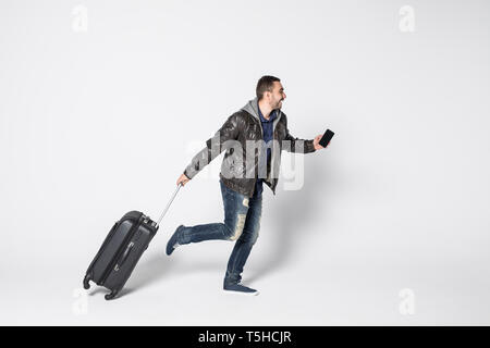 Young man running with bag isolated on white background - Stock Photo