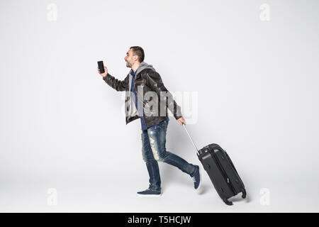 Man with suitcase running on white background. Vacation travel - Stock Photo