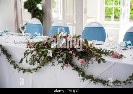 Floral table decorations on a wedding day at the wedding reception venue - Stock Photo