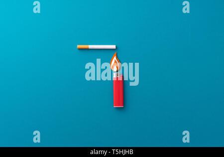 Lighting a cigarette concept over black background - Stock Photo
