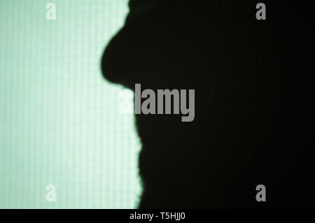 Abstract background shadows of male nose beard mouth on digital wall light from cinema projector on a wall - Stock Photo