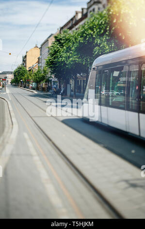 Strasbourg, France - Jun 2, 2012: New modern electric tramway arriving in station streets avenues of Strasbourg on a sunny day - tilt shift lens used  - Stock Photo