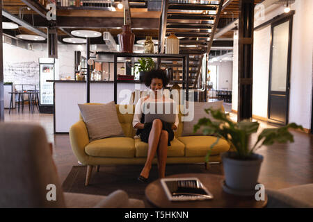 Happy businesswoman sitting on yellow sofa while she is using laptop - Stock Photo