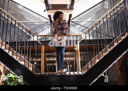 Businesswoman leaning on railing guard while she is talking in mobile phone - Stock Photo