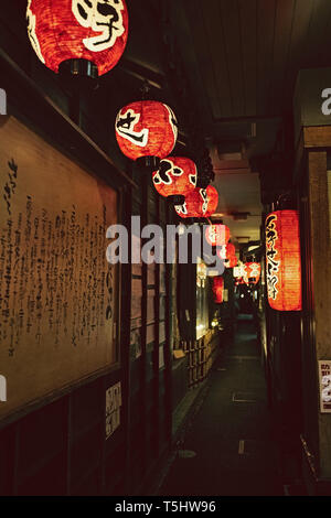 Lanterns illuminating a dark alley at night in Osaka, Japan - Stock Photo
