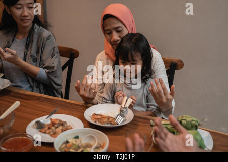 mom and daughter pray before eating - Stock Photo