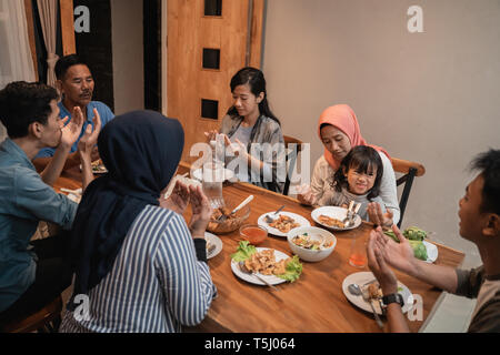 muslim family pray before dinner - Stock Photo
