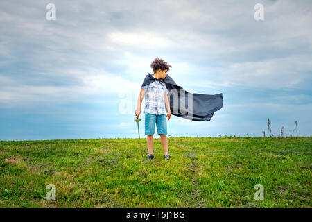 Young boy super hero with blowing cloak standing outdoors in a green field in the wind looking behind to watch it billow in the breeze - Stock Photo