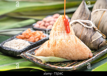 Zongzi, steamed rice dumplings with chili sauce. Close up, copy space, famous asian tasty food in dragon boat duanwu festival - Stock Photo