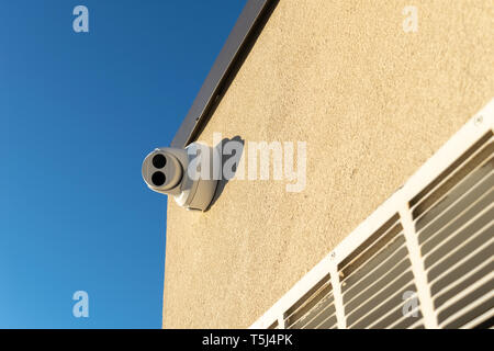 Security camera mounted on a wall, pointed straight at the viewer - Stock Photo