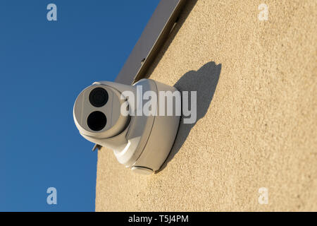 Security camera mounted on a wall, pointed straight at the viewer, close-up - Stock Photo
