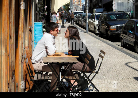 Young romantic couple sitting outside a cafe restaurant at a table on the pavement Rua de Cedofeita city street in Porto Portugal Europe  KATHY DEWITT - Stock Photo