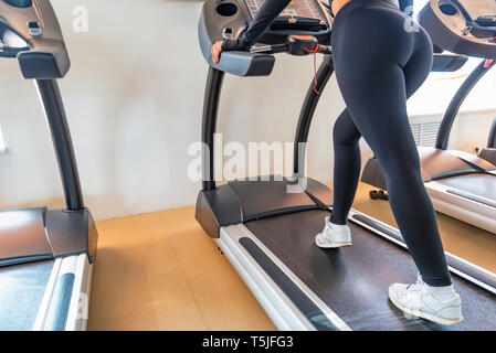 Close up young fit woman on modern treadmill in gym. Lower part view - Stock Photo