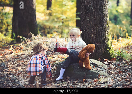 Children put red boots on girl feet. Children getting ready for walk in autumn forest - Stock Photo