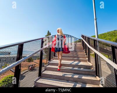 Attractive woman walking downstairs over footbridge foot-bridge looking away wearing Black dress Red scarf handbag high-heeled heels shoes MR - Stock Photo