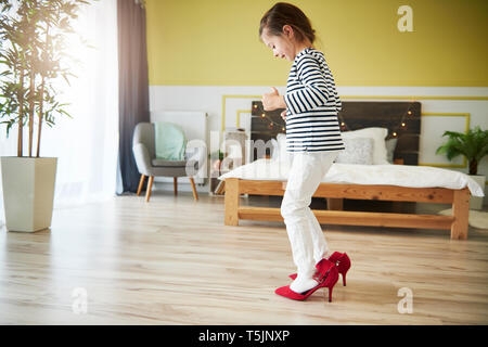 Little girl dressing up, wearing mother's red high heels - Stock Photo