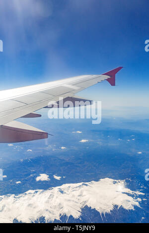 view from the window of the plane that flies over the mountains. - Stock Photo