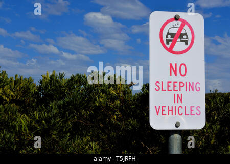 A road sign reads: No sleeping in vehicles. - Stock Photo