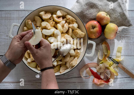 High angle close up of person placing apples in a round baking tin. - Stock Photo