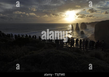 Silhouette of unrecognizable tourists at Port Campbell National Park, looking at the Twelve Apostles during sunset along the Great Ocean Road in Victo - Stock Photo