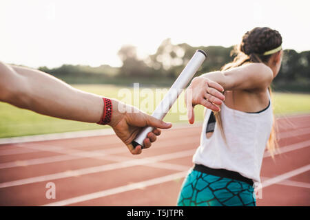 Close-up of a athlete passing the baton to a female athlete - Stock Photo