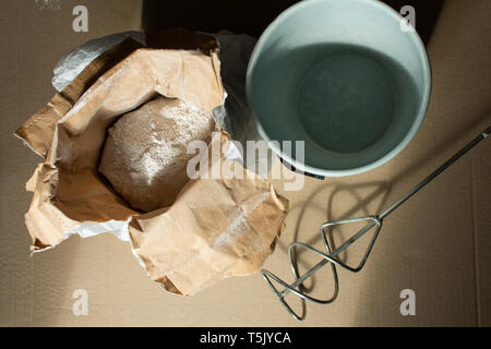 Preparation for construction work, bag with gypsum putty and drill mixer - Stock Photo