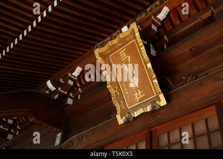A gold plaque sign written 'Maginu Shrine' hangs above main entrance of the building at Maginu shrine, Kawasaki, Japan. - Stock Photo