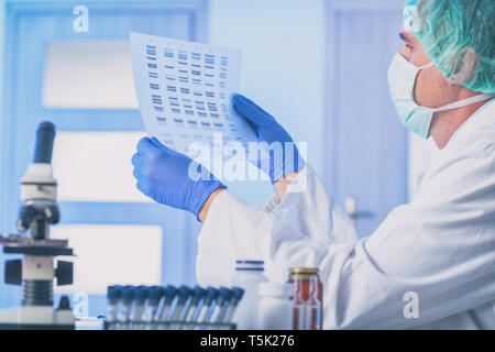 Scientist analizing DNA sequence in the modern laboratory - Stock Photo