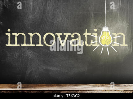 word innovation on chalkboard with glowing light bulb symbolizing and idea - Stock Photo