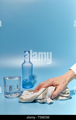 woman cleaning water spilled from a glass on a blue background - Stock Photo